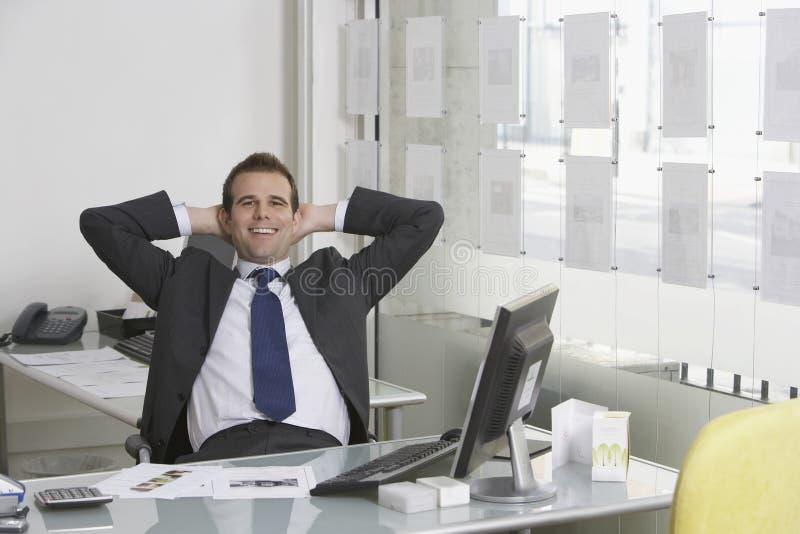 Ontspannen Zakenman Sitting At Desk in Bureau royalty-vrije stock foto's