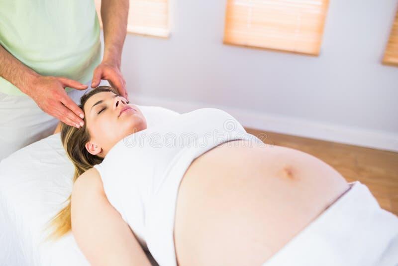 Ontspannen zwangere vrouw die van hoofdmassage genieten stock afbeelding