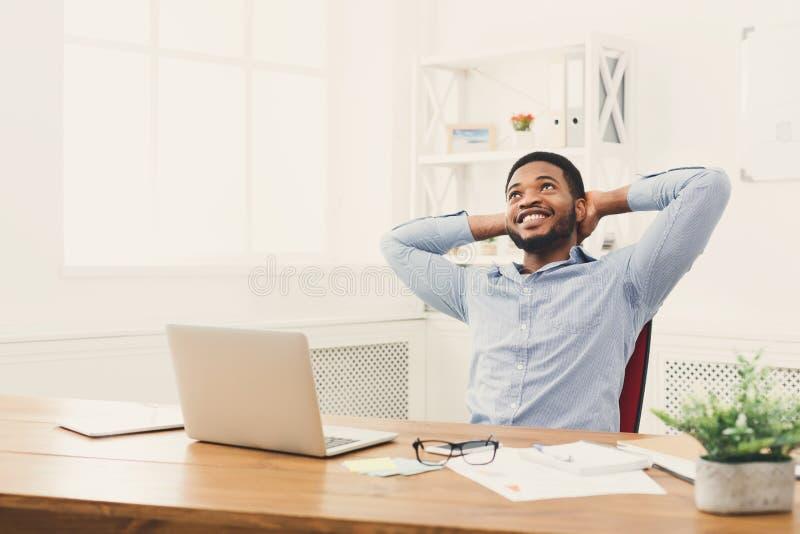 Ontspannen zwarte zakenman in modern wit bureau royalty-vrije stock foto