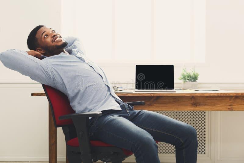 Ontspannen zwarte zakenman in modern wit bureau royalty-vrije stock foto's