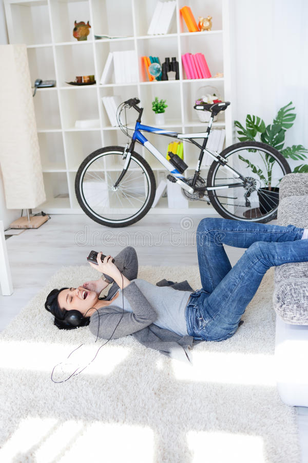 Ontspannend meisje dat op vloer in woonkamer ligt stock afbeeldingen