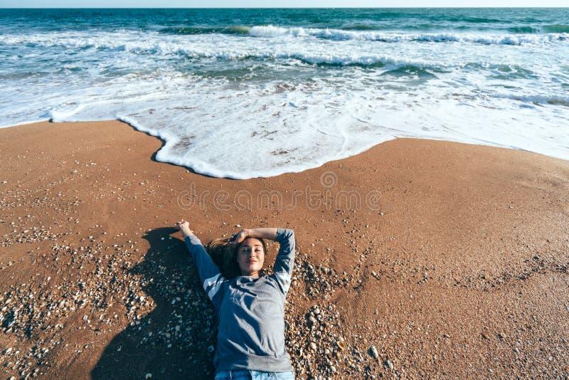 Ontspannend op zand door de overzeese golf, het concept van het dalingsstrand royalty-vrije stock foto's