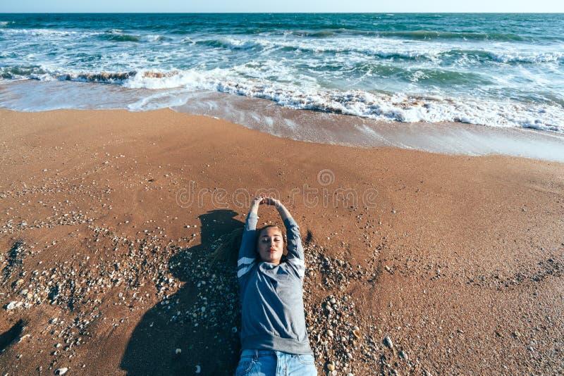 Ontspannend op zand door de overzeese golf, het concept van het dalingsstrand royalty-vrije stock afbeelding
