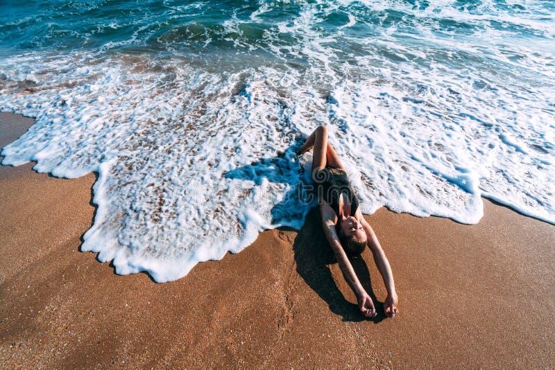 Ontspannend op zand door de overzeese golf, het concept van het de zomerstrand royalty-vrije stock afbeeldingen