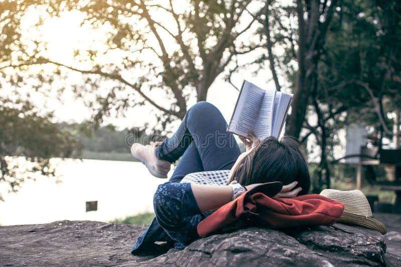 Ontspannende ogenblik Aziatische toerist die een boek op rots lezen royalty-vrije stock afbeeldingen