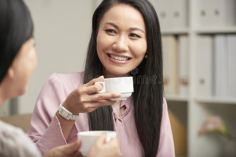 Ontspannende verwantenvrouwen die thee hebben thuis stock afbeeldingen