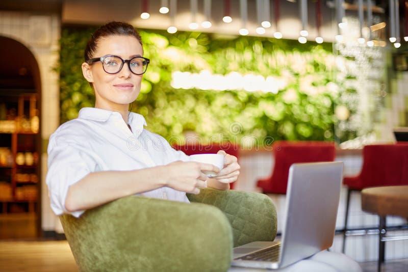 Ontspannende vrouw met koffie en laptop stock foto's