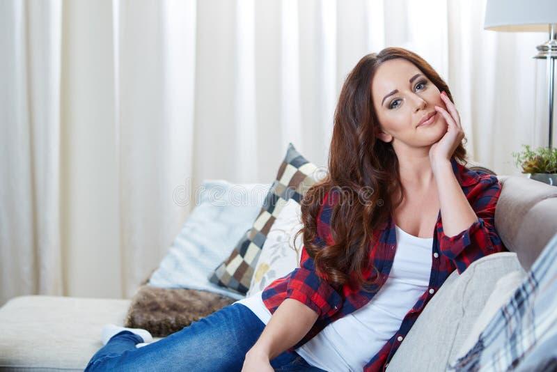 Ontspannende vrouwenzitting comfortabel in bankzitkamer stock foto's