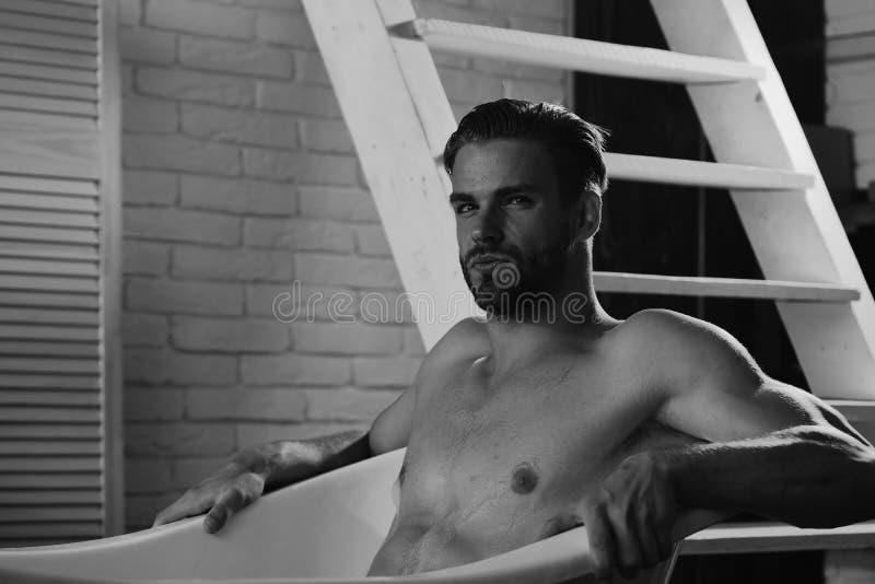 Ontspanning en eroticaconcept Machozitting die naakt en in badkuip, selectieve nadruk ontspannen stock afbeeldingen