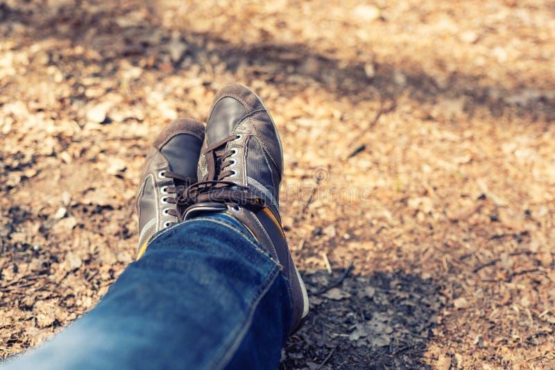 Ontspanning na het lopen in bosclose-upbenen in blauwe toevallige jeans en bruine leerlaarzen Avontuur en reisconcept stock foto's