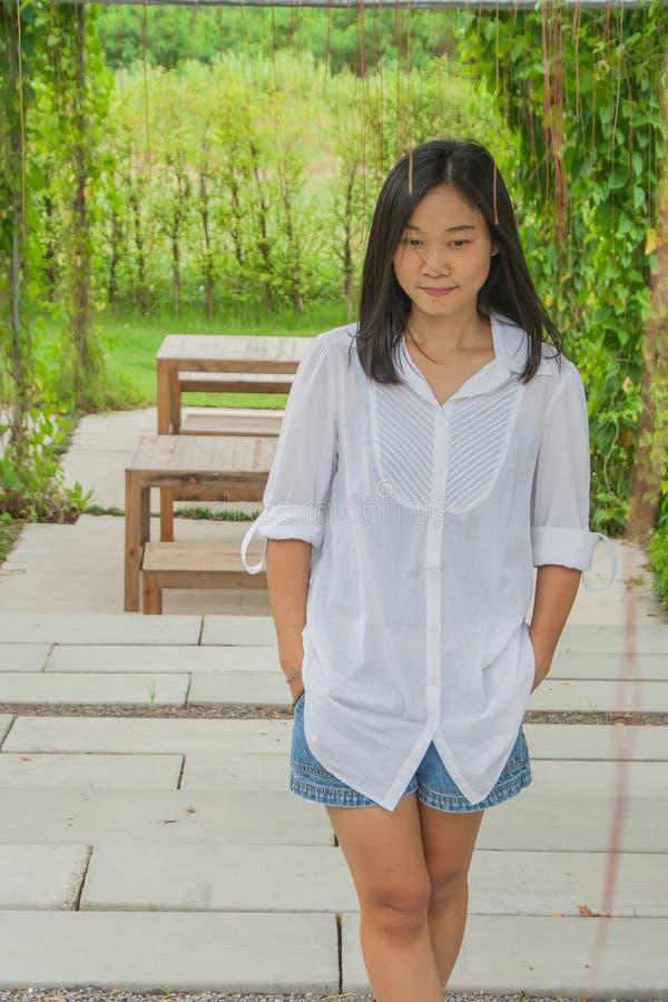 Ontspanningsconcept: Het Aziatische witte overhemd die van de vrouwenslijtage zich op cementvloer bij openluchttuin bevinden royalty-vrije stock foto's