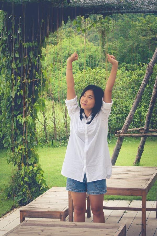 Ontspanningsconcept: Het Aziatische witte overhemd en de rek van de vrouwenslijtage in de tuin royalty-vrije stock foto