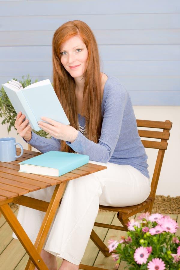 Ontspant de het terras redhead vrouw van de zomer met boek stock afbeeldingen