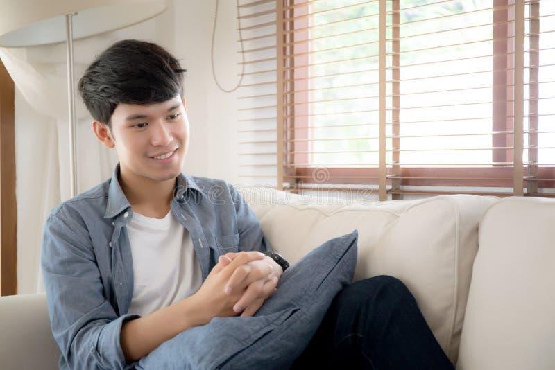Ontspant de portret jonge knappe Aziatische mens die thuis met comfortabel bij bank, het mannelijke rusten van Azië en slapen dut royalty-vrije stock foto