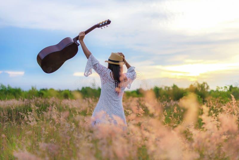 Ontspant de witte kleding die van levensstijlvrouwen een gitaar op een bewolkte zonsondergang of zonsopganghemel in de weidebloem royalty-vrije stock fotografie