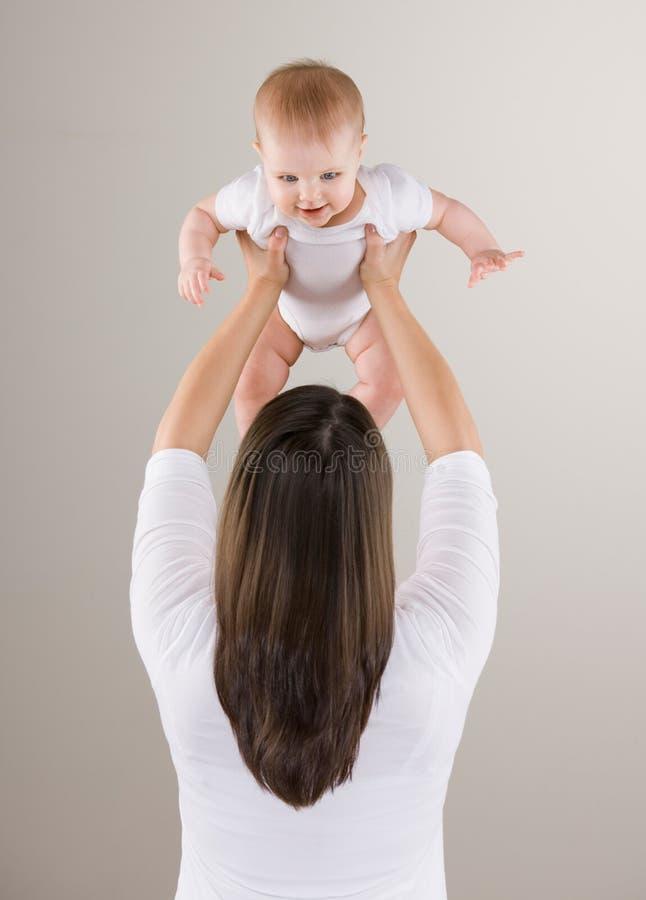 Ontsproten van het houden van moeder van opheffende baby boven hoofd royalty-vrije stock foto