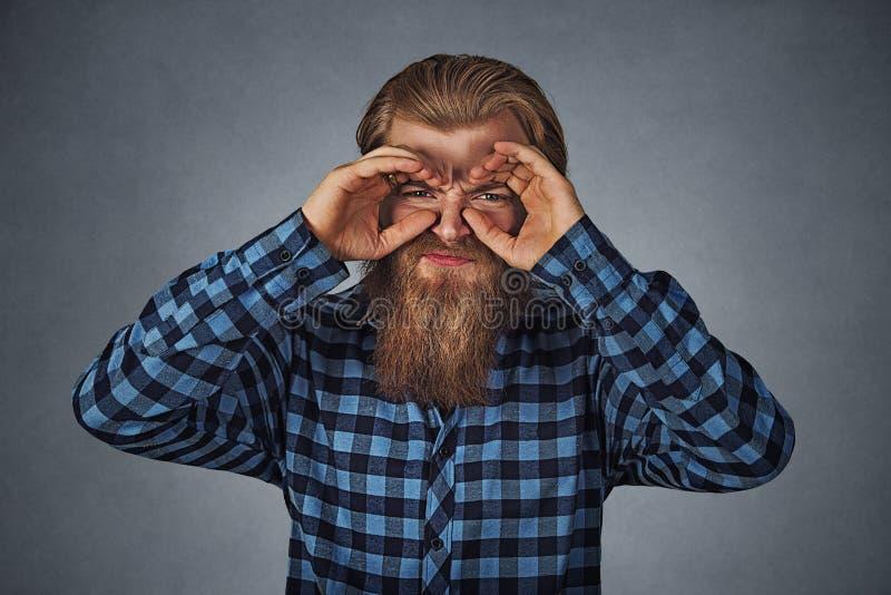 Ontstemde jonge mens die door vingers zoals verrekijkers kijken royalty-vrije stock foto's
