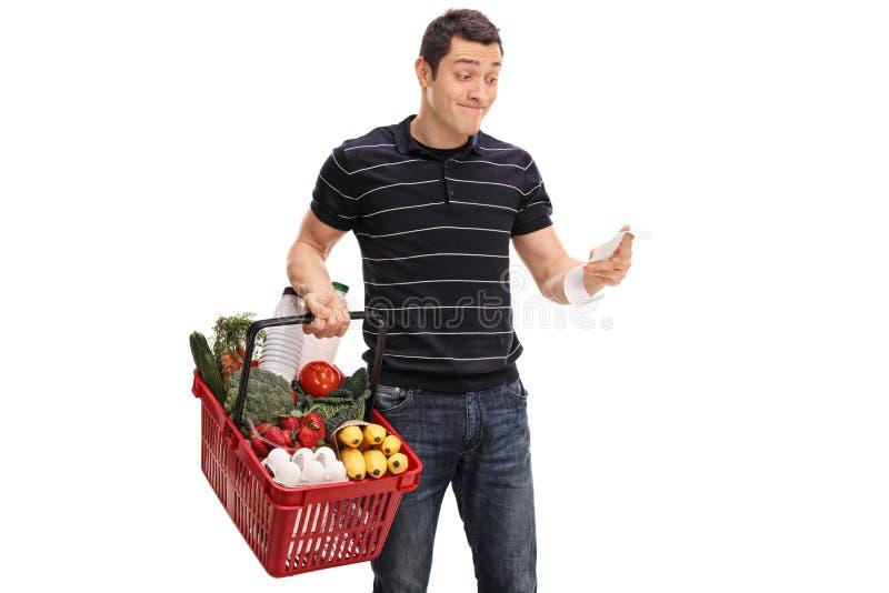 Ontstemde kerel die de het winkelen rekening bekijken stock fotografie