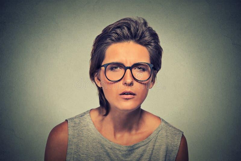 Ontstemde onzekere betwistbare verdachte denkende jonge dame in glazen stock foto