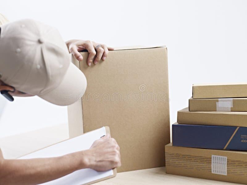 Ontvangend bediende die ontvangen pakketten controleren stock foto