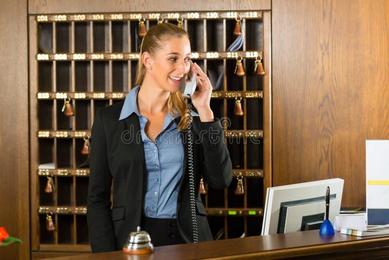 Ontvangst van hotel - bureaubediende die een vraag nemen royalty-vrije stock foto