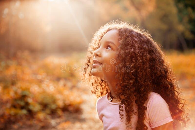 Ontvangt het Afro Amerikaanse leuke meisje met krullend haar de stralen van de mirakelzon van de hemel stock afbeelding