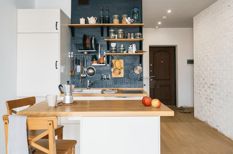 Ontwerp van moderne huiskeuken in de zolder en rustieke stijl Zwarte muur met planken, dienbladen, kruiken, mokken Ijskast, die t royalty-vrije stock afbeeldingen
