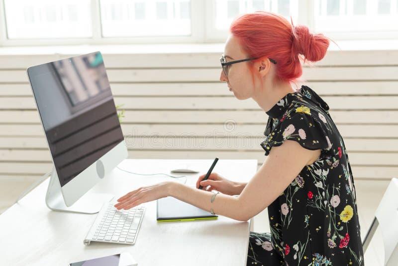 Ontwerper, creatief, mensenconcept - de rode ontwerper die van de haarvrouw een project op een grafische tablet doen royalty-vrije stock foto