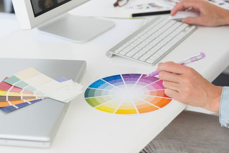 Ontwerper die bij haar bureau werken die een kleurenwiel gebruiken stock foto's