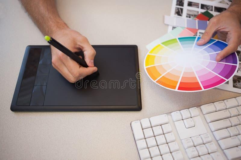 Ontwerper die grafiektablet en kleurenwiel gebruiken royalty-vrije stock afbeeldingen
