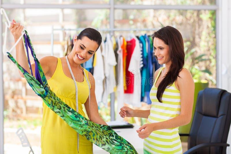 Ontwerper die kleding tonen aan klant stock foto