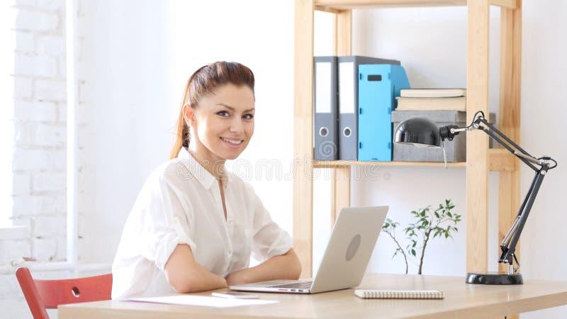 Ontwerper Woman die op het Werk naar Camera glimlachen stock afbeeldingen