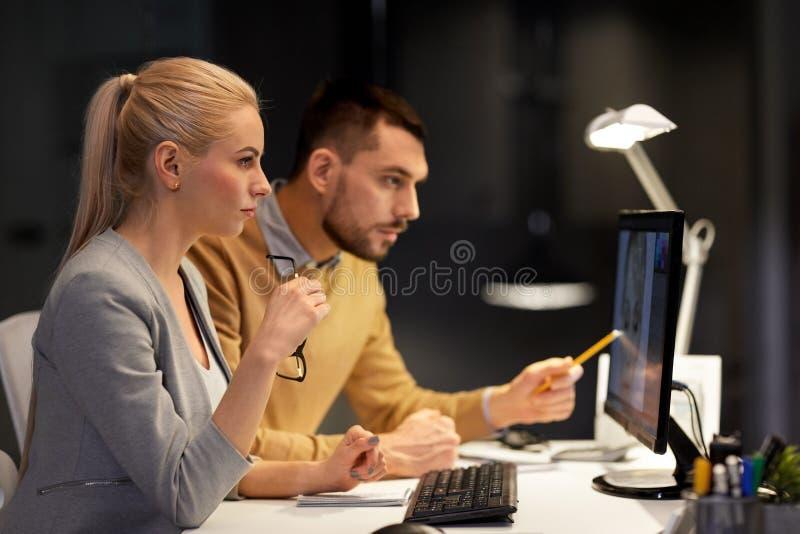 Ontwerpers met computer die op nachtkantoor werken stock foto