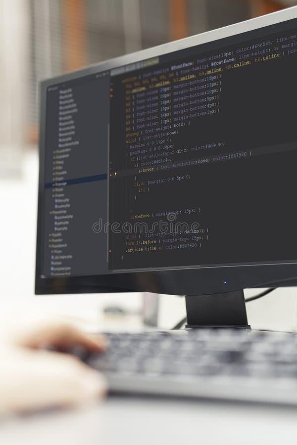 Ontwikkelaar die aan broncodes inzake computer op kantoor werken stock afbeelding