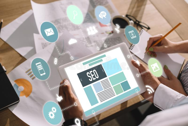 ontwikkelaars die digitale tablet met SEO-symbolen gebruiken stock foto
