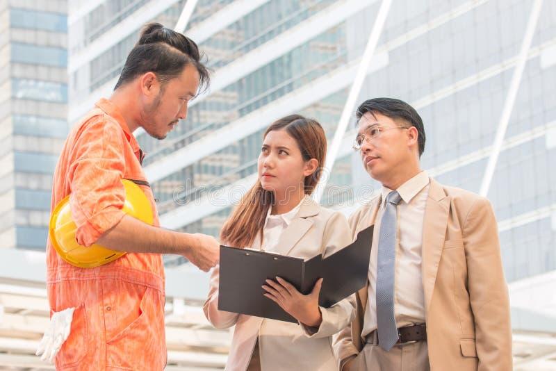 Ontwikkelaars die over een stedelijk panorama kijken die een aangewezen bouwwerf kiezen stock foto