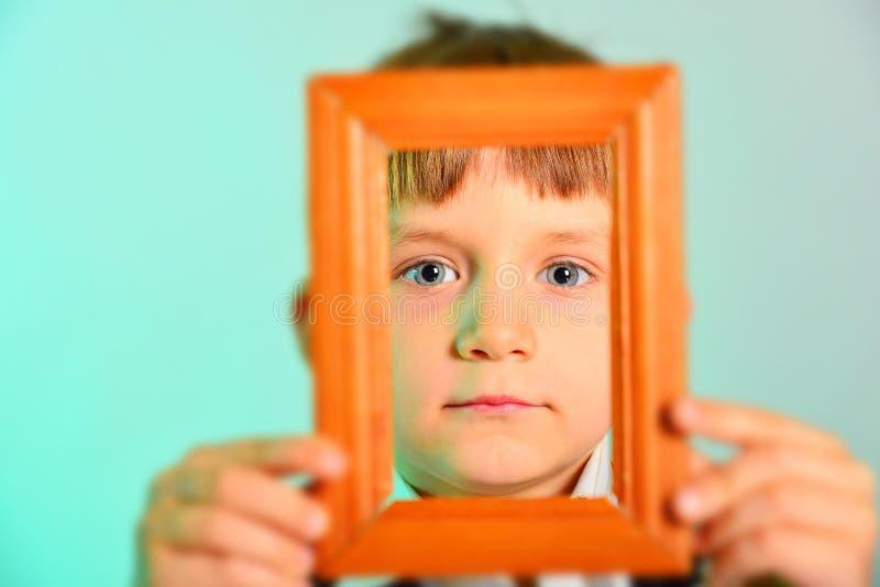 Ontworpen het gezicht, jongen houdt houten kader dichtbij gezicht, close-up stock foto's
