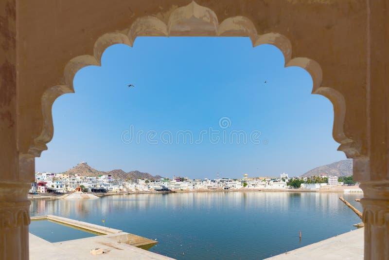 Ontworpen mening van overwelfde galerij in Pushkar, Rajasthan, India Tempels, gebouwen en ghats op het wijwater van het meer bij  royalty-vrije stock fotografie