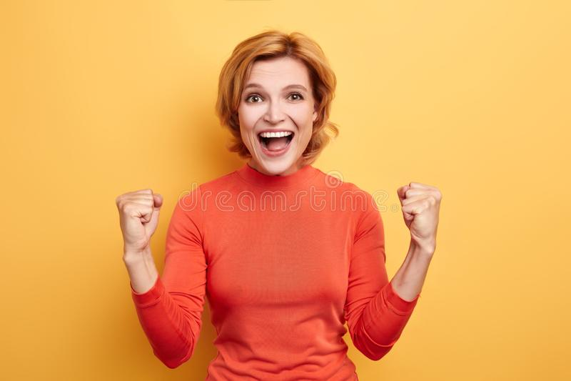 Ontzagwekkend meisje die in rode modieuze broodje-hals sweater zich bij de overwinning van haar team verheugen stock foto's