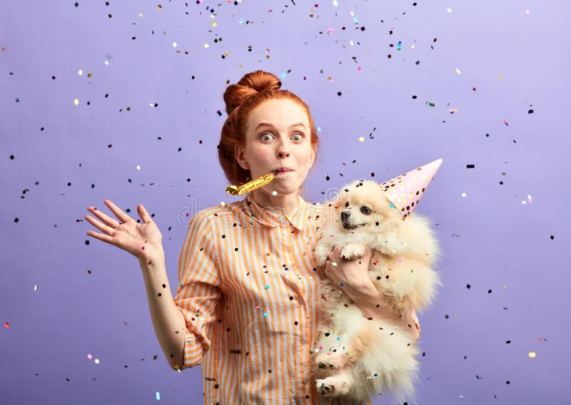 Ontzagwekkend meisje die zich bij verjaardagspartij verheugen van haar hond royalty-vrije stock afbeelding