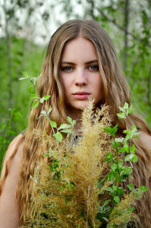 Ontzagwekkend, uitstekend, mooi, aardig meisje met lang, rechtstreeks, wat beetje krullend licht haar met bloemen in openlucht in stock foto's