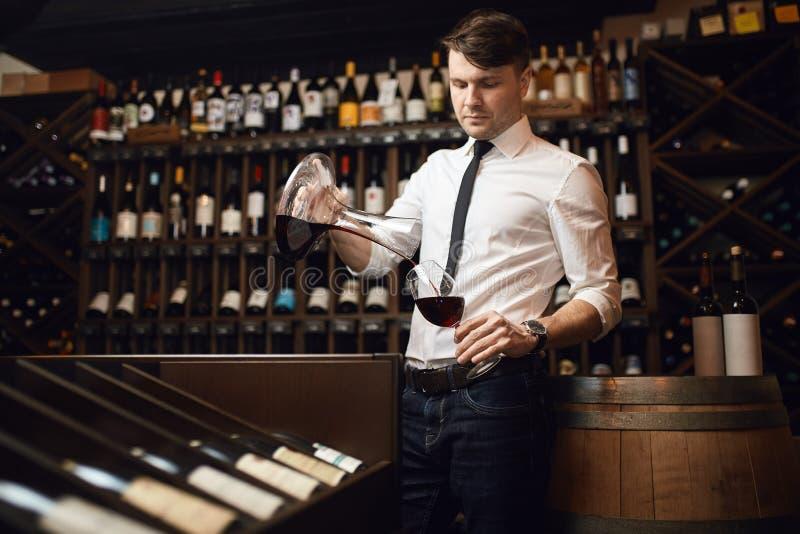 Ontzagwekkende knappe meer sommelier gietende wijn in het glas royalty-vrije stock foto's