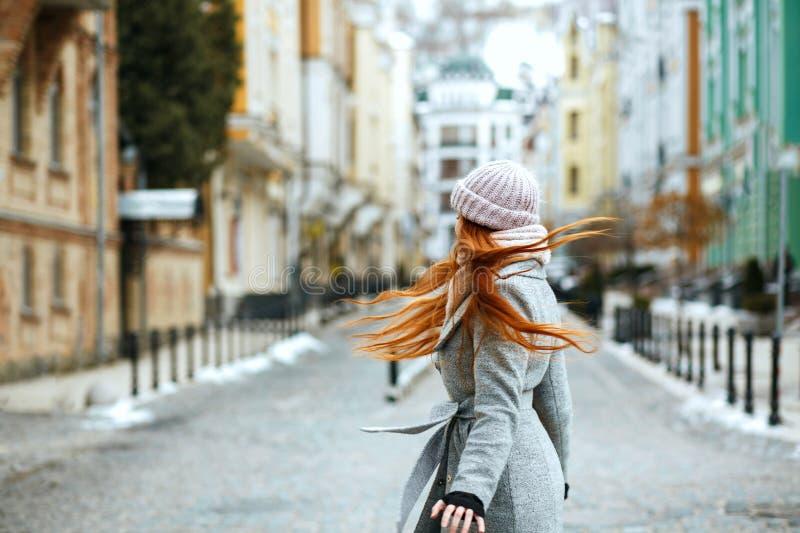 Ontzagwekkende roodharigedame die modieuze de winteruitrusting dragen die in ci lopen royalty-vrije stock fotografie