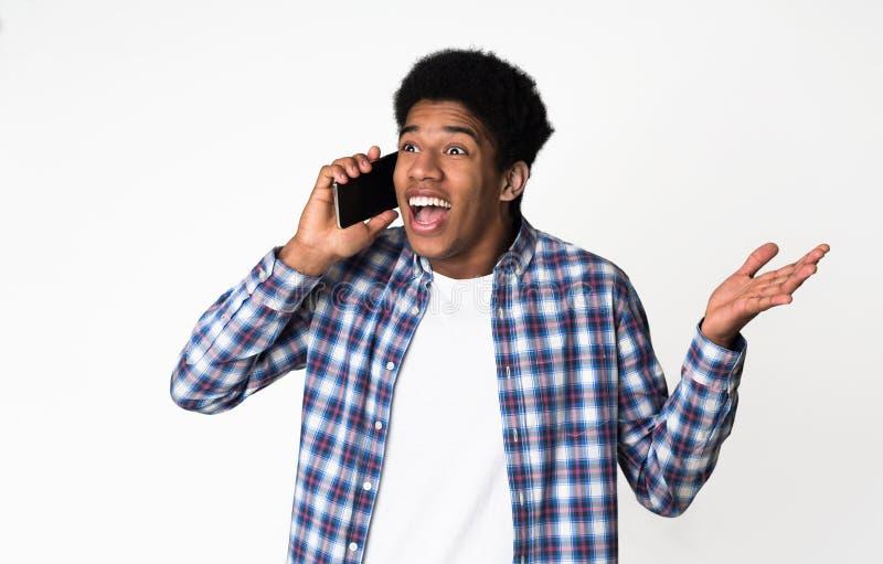 Onverwachte vraag Verraste kerel die op telefoon spreken royalty-vrije stock afbeeldingen