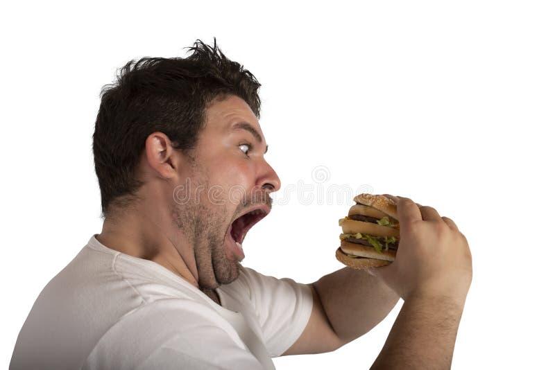 Onverzadigbare en hongerige mens die een sandwich eten royalty-vrije stock afbeelding