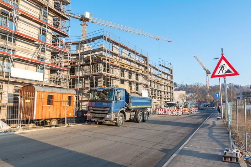 Onvolledig flatgebouw met bouwvoertuigen, steiger en bouwwerfteken stock afbeelding