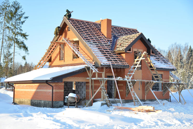 Onvolledig huis van baksteenplaats in aanbouw met houten ro stock afbeelding