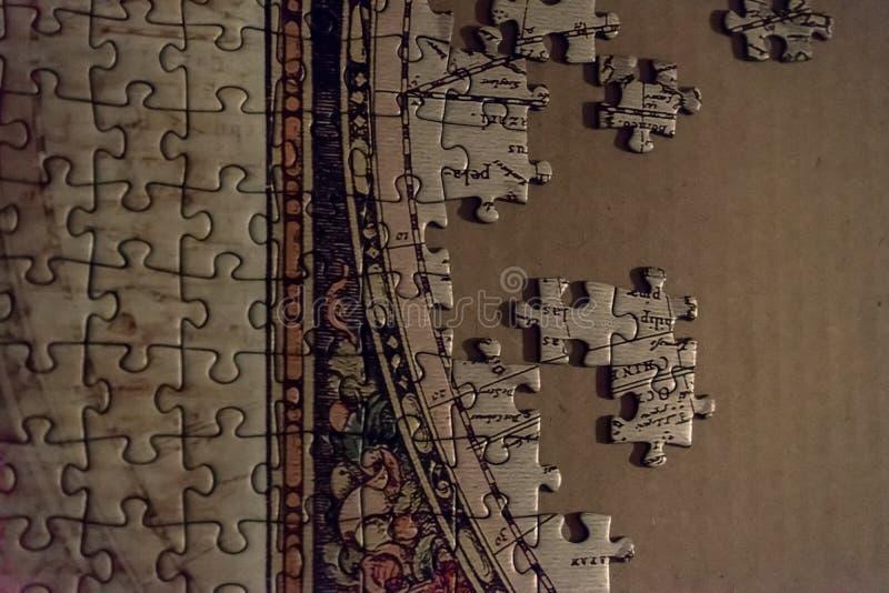 Onvolledig wit Jong geitjeraadsel in proces over een karton als achtergrond stock foto