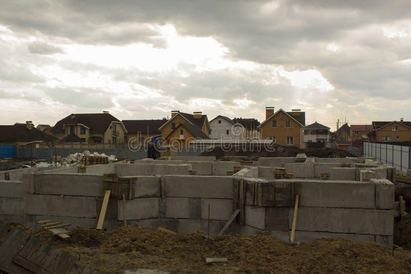 Onvolledige bouw van nieuw huis tegen reeds gebouwde huizen Het concept van de bouw royalty-vrije stock fotografie