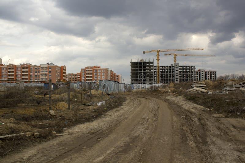 Onvolledige bouwconstructie tegen reeds gebouwde huizen Het concept van de bouw royalty-vrije stock afbeeldingen